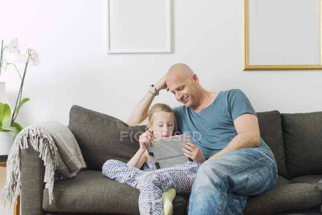 Father doing homework with daughter at home — Stock Photo