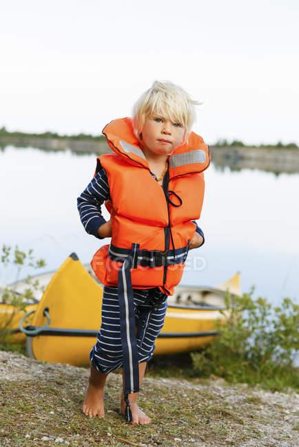 Хлопчик блондинка носіння жилету стоїть на березі річки — стокове фото