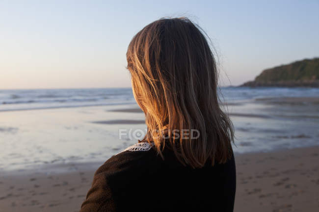 Woman standing on beach and looking at Bay of Biscay at sunset — Stock Photo
