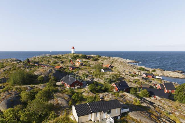 Farol em rochas no mar Báltico com a Estalagem vermelha em primeiro plano — Fotografia de Stock