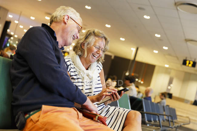 Älteres Paar mit Smartphone in Flughafen — Stockfoto