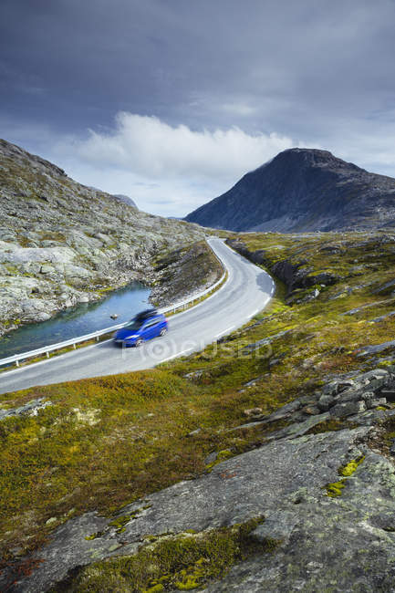 Motion blurred blue car driving along winding section of Trollstigen road — Stock Photo