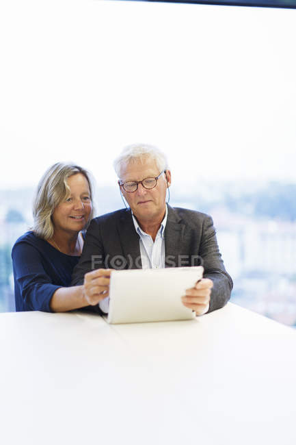 Two business people using laptop in office, focus on foreground — Stock Photo