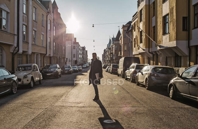 Man standing in sunlit street, diminishing perspective — Stock Photo