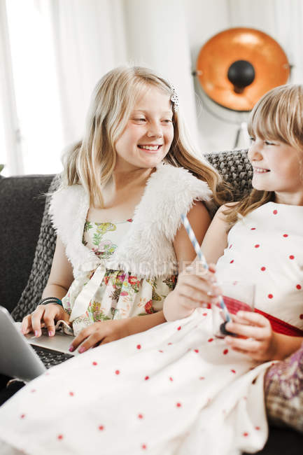 Girls laughing and using laptop on sofa, selective focus — Stock Photo