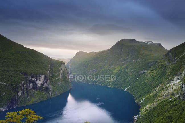 Vue du lac et des montagnes vertes couverts sous ciel nuageux — Photo de stock