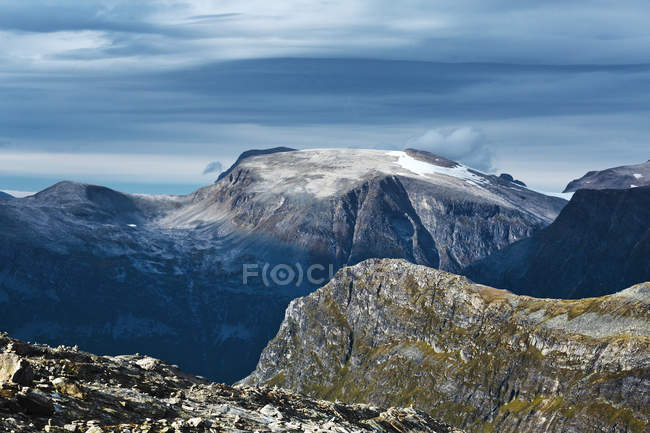 Snowcapped rocky mountains under cloudy sky — Stock Photo