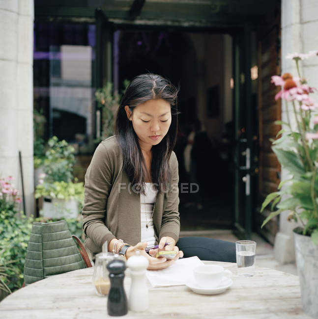 Woman sitting at cafe and text messaging — Stock Photo