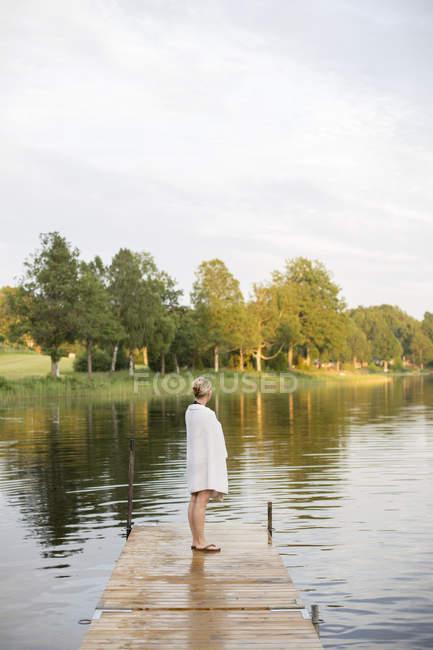 Mulher madura envolto em toalha de pé no molhe — Fotografia de Stock