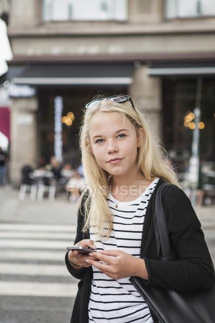 Adolescente che utilizza smartphone sulla strada — Foto stock