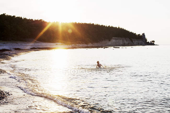 Boy swimming in ocean at sunset, lens flare — Stock Photo