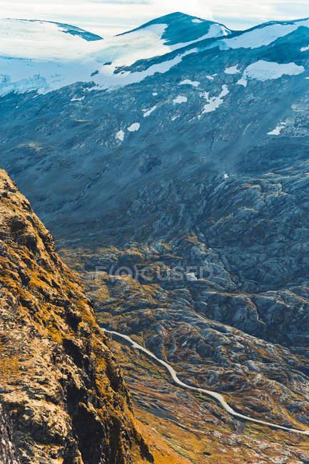 Route qui s'étend à travers vallée de montagne éclairée de soleil — Photo de stock