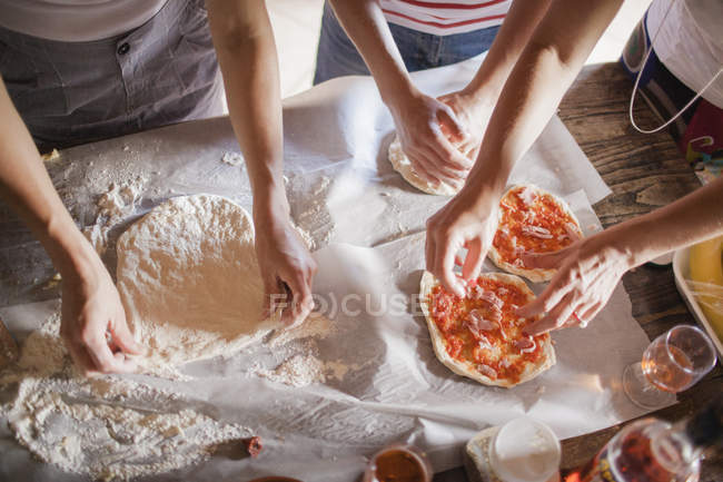 Women preparing homemade pizzas on table — Stock Photo