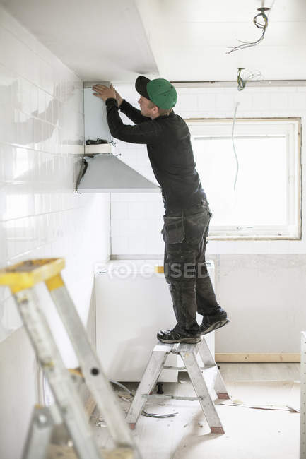 Side view of carpenter installing kitchen furniture — Stock Photo