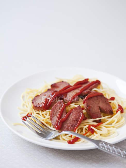 Porción de pasta con pepperoni y ketchup en el plato - foto de stock