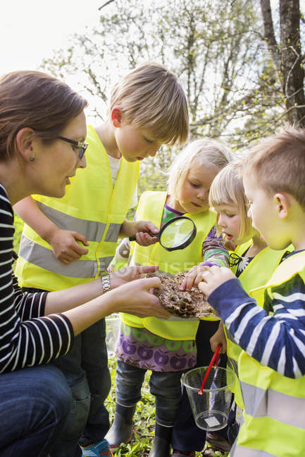 Woman taking care of children outdoors — Stock Photo