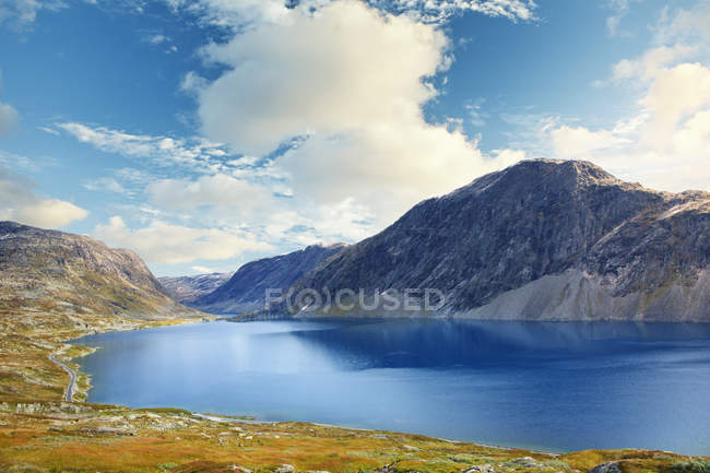 Calm bay and mountains under cloudy sky in sunlight — Stock Photo