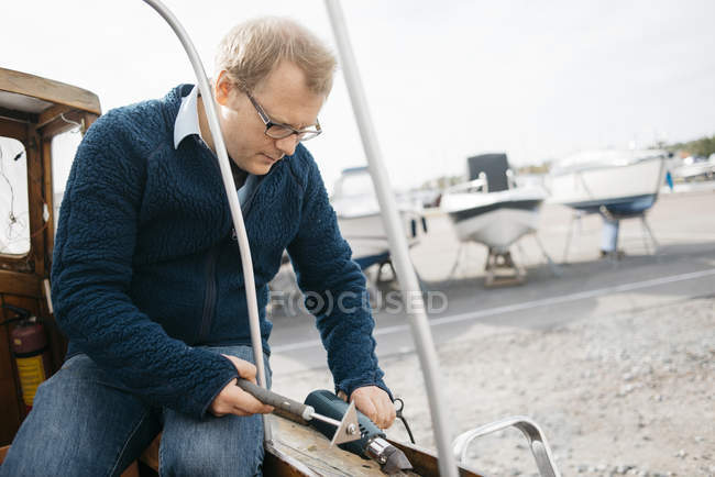 Man renovating wooden boat with tool — Stock Photo