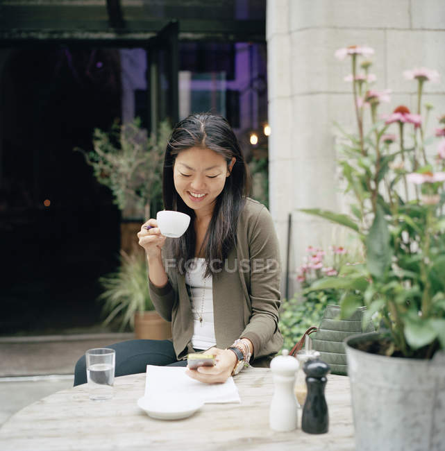 Smiling woman sitting at cafe and text messaging — Stock Photo