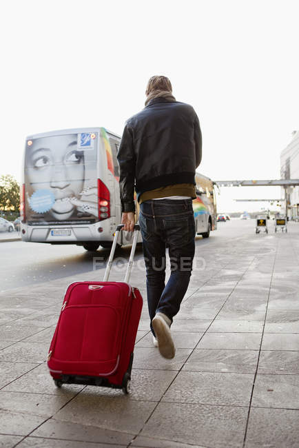 Rear view of man pulling suitcase — Stock Photo