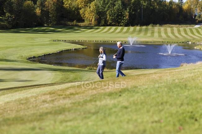 Senior homme et femme d'âge mûr marchant dans le parcours de golf — Photo de stock