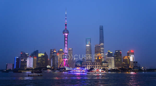 Financial district in Shanghai with Huangpu river in foreground illuminated at night — Stock Photo