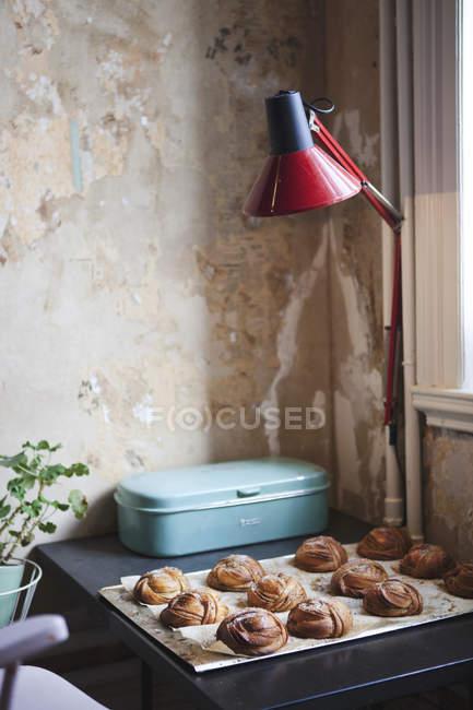 Table with fresh baked cardamon buns — Stock Photo
