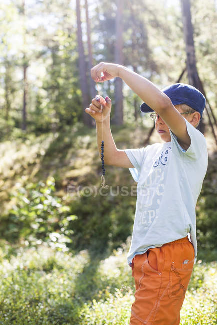 Boy threading blueberries on string, selective focus — Stock Photo
