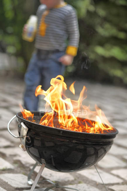 Focus on barbecue grill with boy in background — Stock Photo