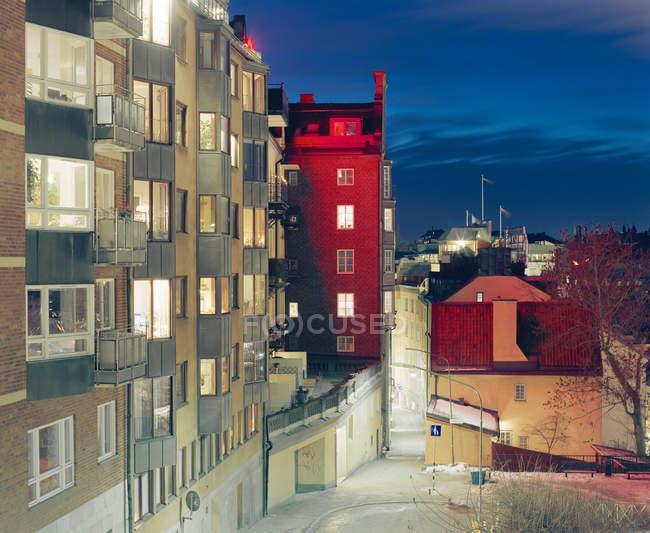 Apartment buildings with windows illuminated at night — Stock Photo