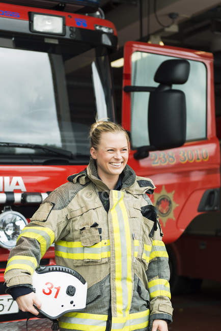 Smiling female firefighter holding helmet by fire engine — Stock Photo