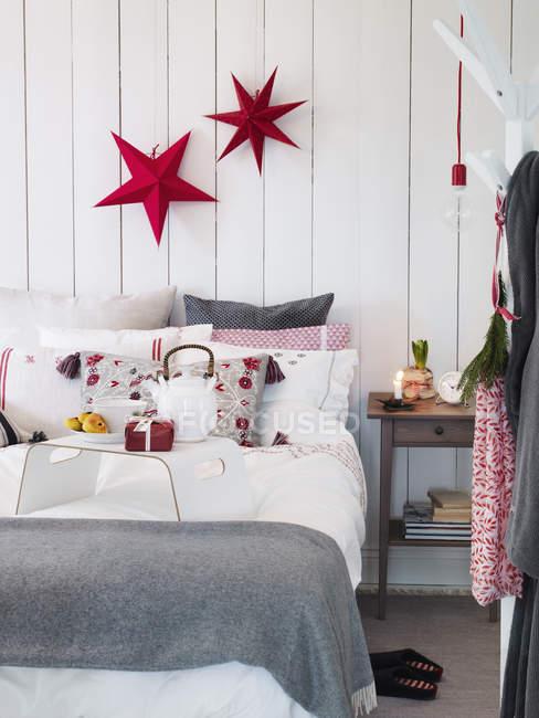 Schlafzimmer mit Weihnachtsschmuck und Geschenk auf Bett — Stockfoto