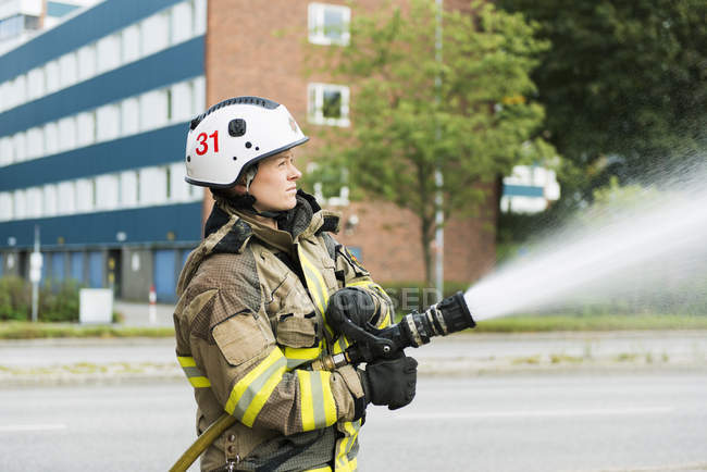Female firefighter using fire hose in street — Stock Photo