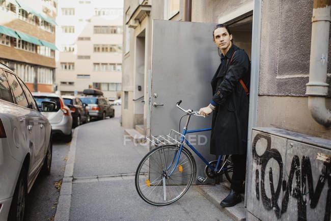 Jeune homme, laissant la maison à vélo — Photo de stock