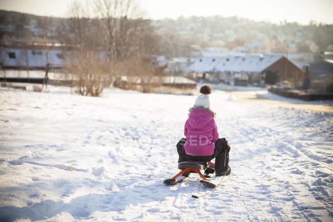Vue arrière de fille luge sur route enneigée avec la physionomie d'une ville en arrière-plan — Photo de stock