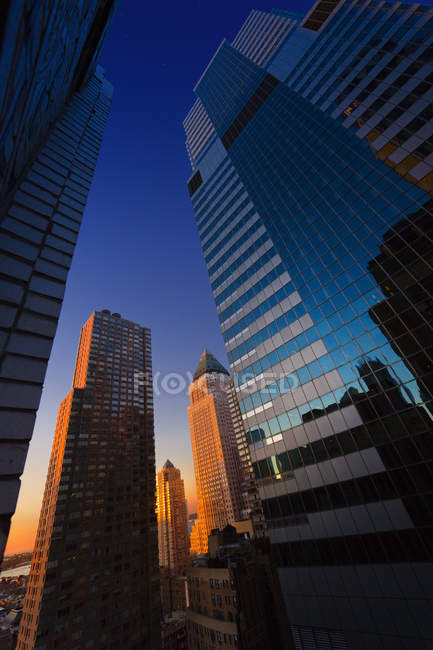 Upward view of skyscrapers against sunset sky at Manhattan, New York — Stock Photo