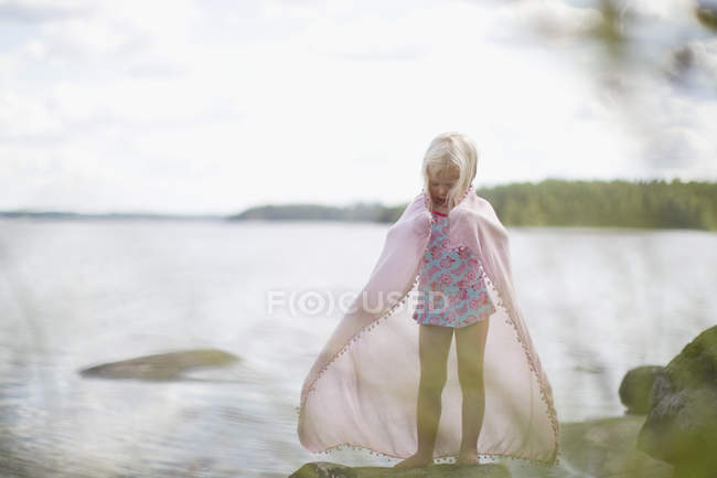 Girl standing beside lake, differential focus — Stock Photo