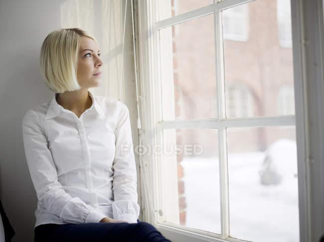 Frau sitzt auf Fensterbank und schaut durch Fenster — Stockfoto