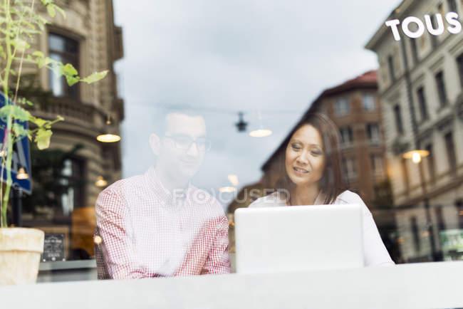 Hombre y mujer hablando en la cafetería con el ordenador portátil - foto de stock