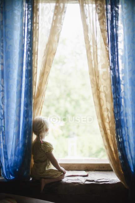 Garota com cabelo loiro, olhando pela janela — Fotografia de Stock