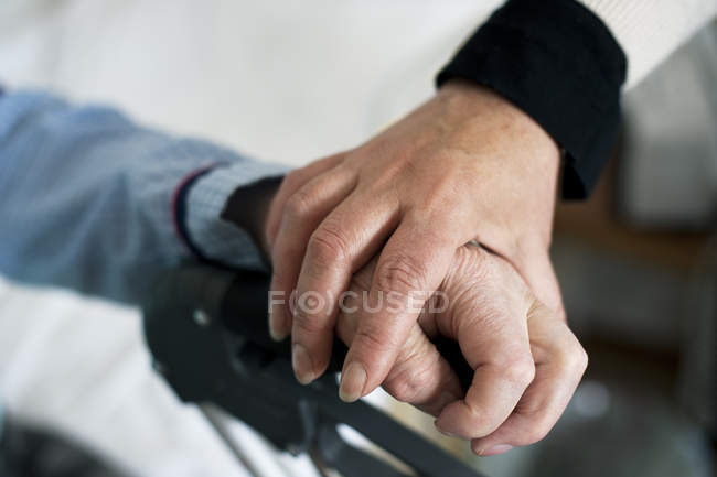 Close-up of female hand holding senior patients hand, selective focus — Stock Photo