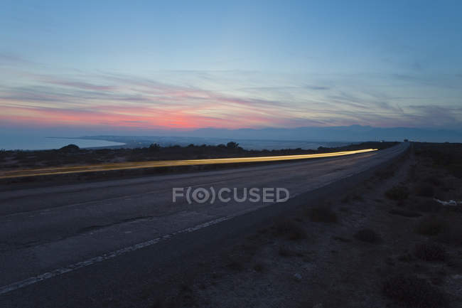 Light trail on road under cloudy sunset sky — Stock Photo