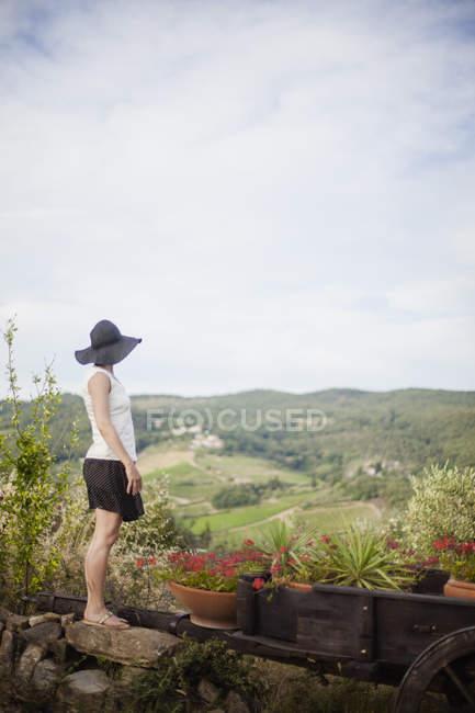 Vista lateral da mulher de chapéu preto olhando para a paisagem — Fotografia de Stock