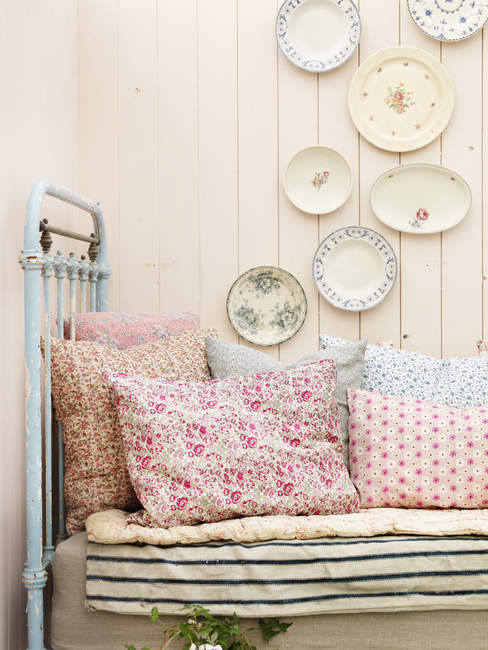 Vintage bed and wall decorated with plates — home interior ...