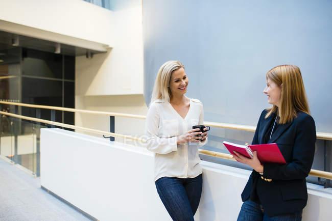 Два предпринимателей, говорят в коридоре офиса — стоковое фото