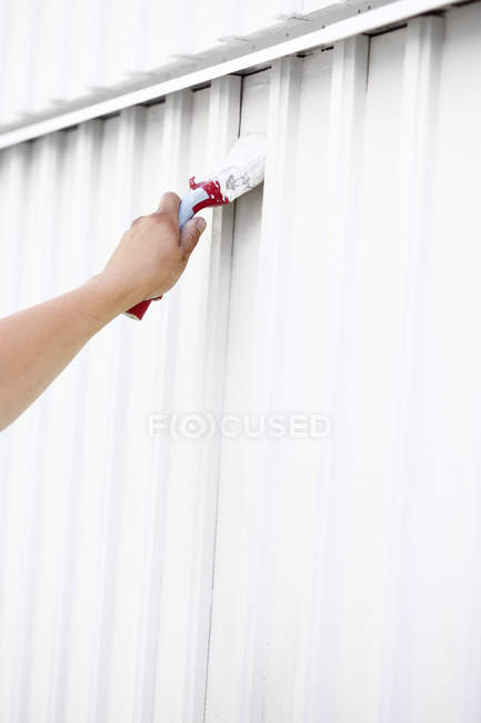 Hand painting wall in white color with brush — Stock Photo