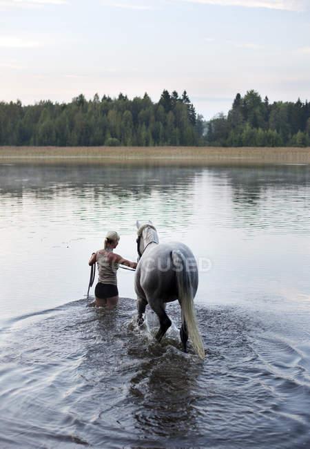 Vista posteriore della donna che conduce il cavallo in Lago — Foto stock