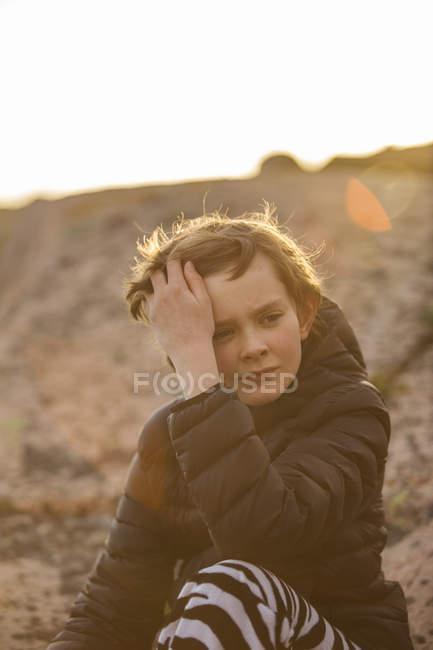 Triste garçon assis dehors au coucher du soleil, foyer sélectif — Photo de stock