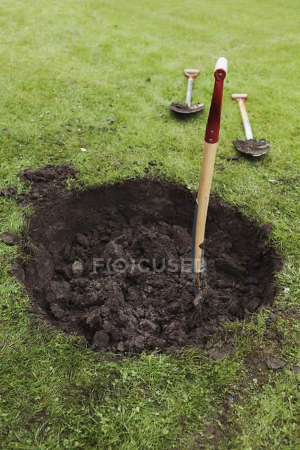 Повышенный вид лопаты в земле на зеленом поле — стоковое фото