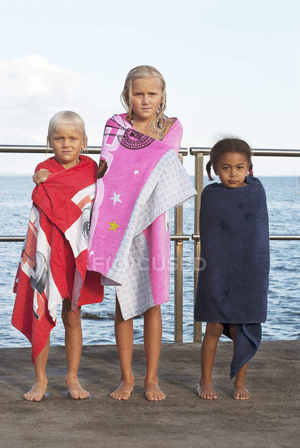 Boy and two girls wrapped in towels on jetty — Stock Photo
